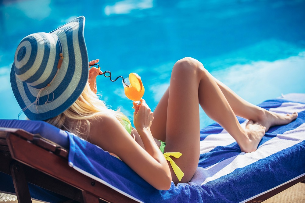 Portrait of young woman with cocktail glass chilling in the tropical sun near swimming pool on a deck chair