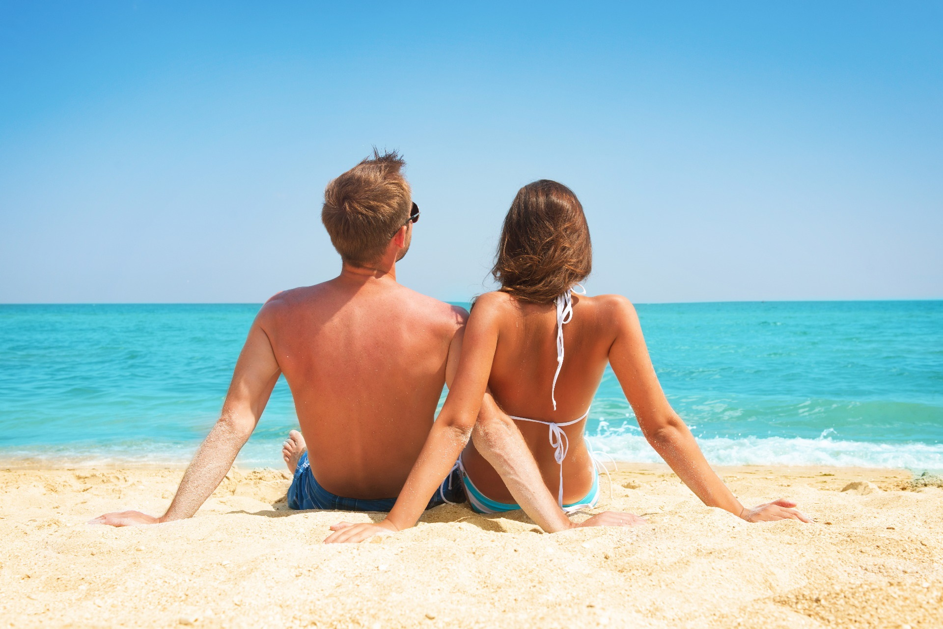 Young Couple Sitting together on the Beach. Vacation concept